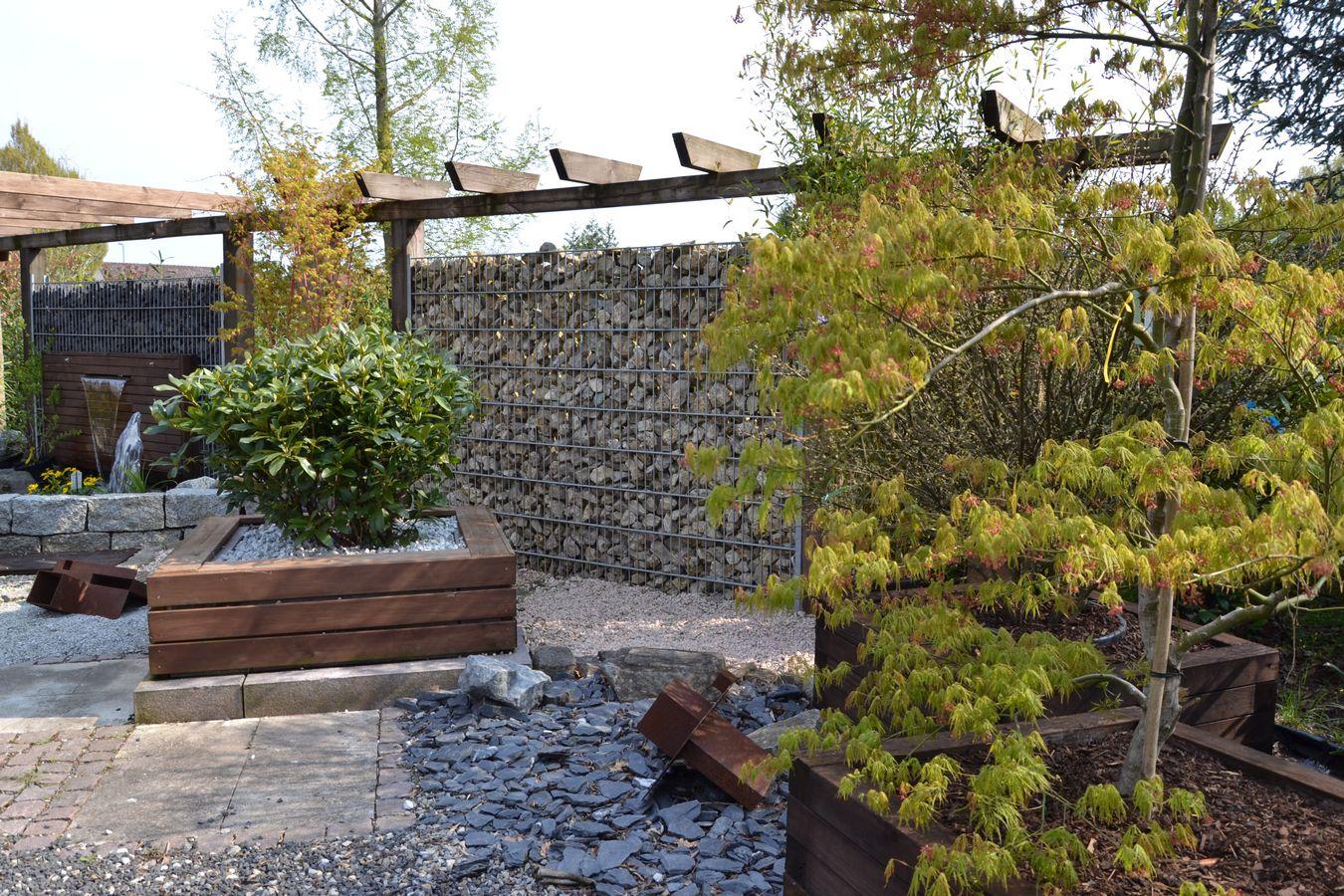 Pflanztröge aus Holz vor Gabionenzaun