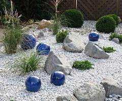 Bunte Glaskugeln als Dekoelemente auf Kies mit Findlingen