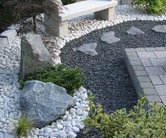 Variantenreiche Steinkombination mit Sitzbank im pflegeleichten Garten