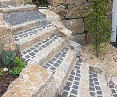 Rustikal gemauerte Gartentreppe aus Basaltpflaster und behauenen Natursteinen