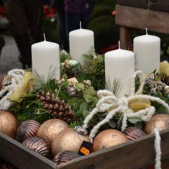 Kranz mit weißen Kerzen und Schleifenelementen
