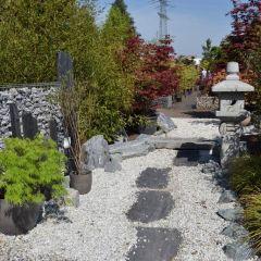 Über hellen Kies führen Schieferplatten zu einer Steinpagode vorbei an Basaltstelen
