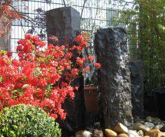 Behauene Basaltquellsteine mit Ahorn, Bux und Rhododendron