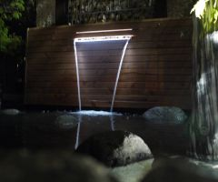 In der Dämmerung wird der Wasserfallbrunnen beleuchtet.