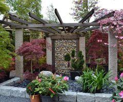 Eine Pergolakonstruktion wird durch reiche Bepflanzung bereichert.