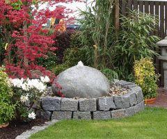 Im kleinen hochgelegten Kiesbeet sprudelt ein runder Quellstein.