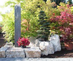 Große Bruchsteine aus Naturstein und eine große Stele im asiatischen Garten