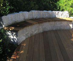 Kreative halbrunde Steinbank aus behauenen Natursteinen
